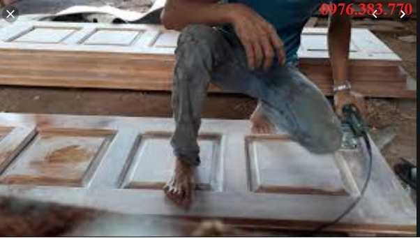 Dùng máy chà nhám bề mặt trước khi sơn cửa gỗ